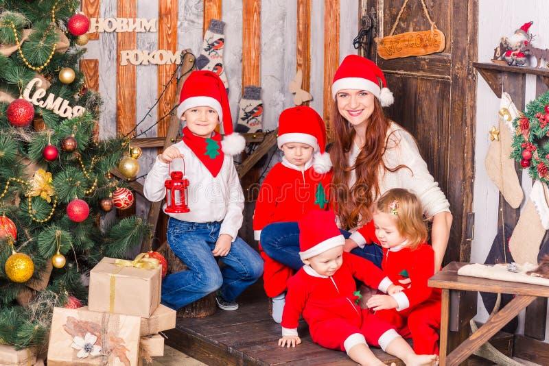 Den lyckliga familjen i jultomten` s kostymerar nära Xmas-träd royaltyfri fotografi