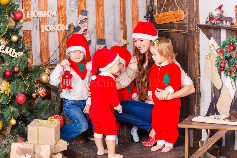 Den lyckliga familjen i jultomten` s kostymerar nära Xmas-träd arkivfoto