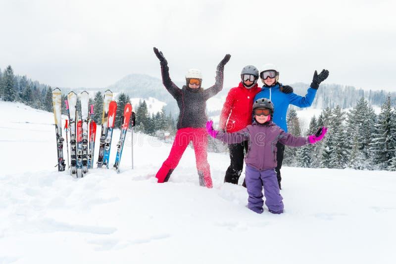 Den lyckliga familjen i vinterkläder på skidar semesterorten - skidåkning, vintern, snö, gyckel - mamman och döttrar som tycker o fotografering för bildbyråer