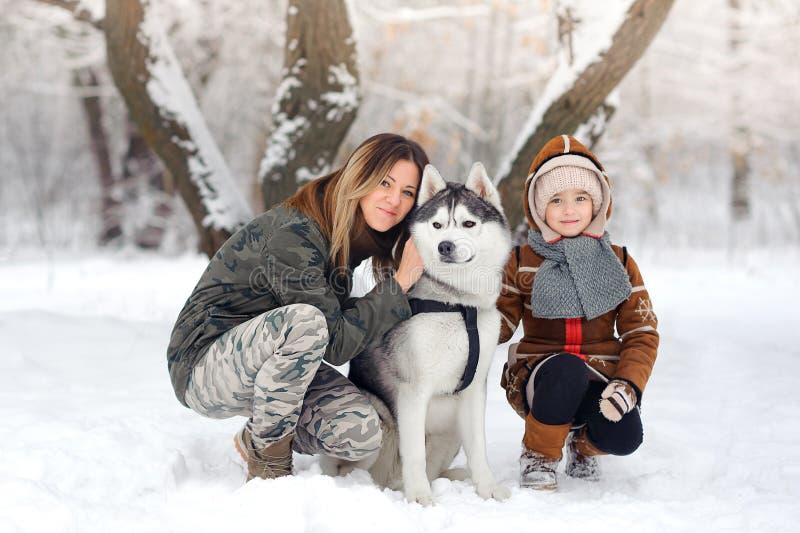 Den lyckliga familjen i vintern parkerar royaltyfri bild