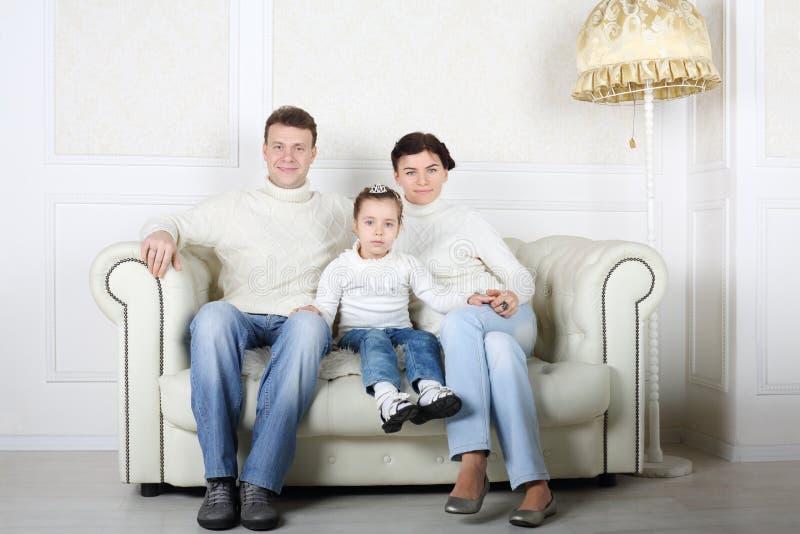 Den lyckliga familjen i vita tröjor och jeans sitter på den vita soffan arkivbilder