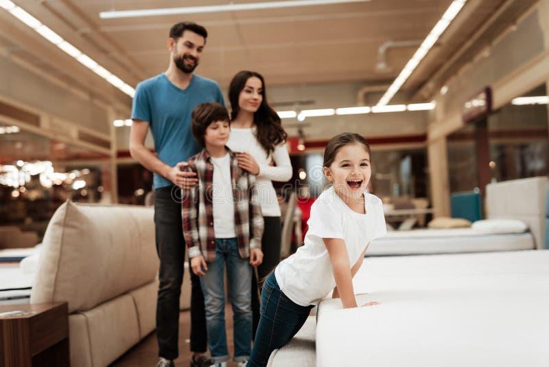 Den lyckliga familjen köper den nya ortopediska madrassen i möblemanglager Lycksalig familj som väljer madrasser i lager royaltyfri foto