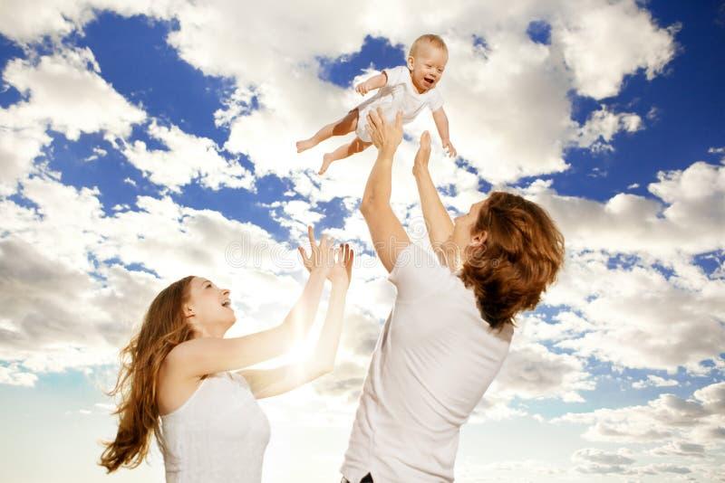 Den lyckliga familjen kastar behandla som ett barn upp pojken mot blå himmel fotografering för bildbyråer