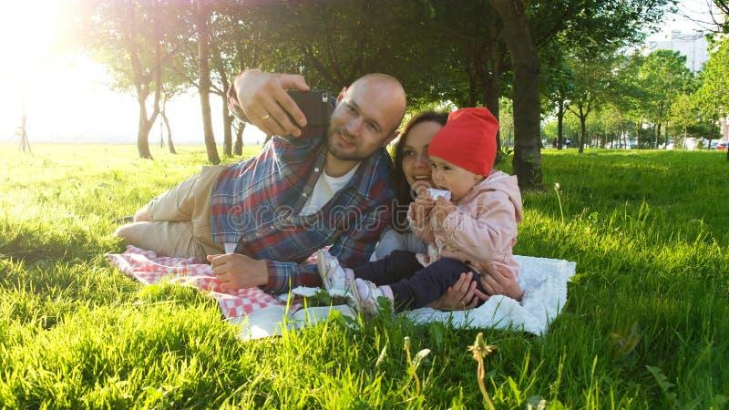 Den lyckliga familjen lägger på gräset och gör selfie med en behandla som ett barn på solnedgången i parkera Fadern och modern ta royaltyfri foto