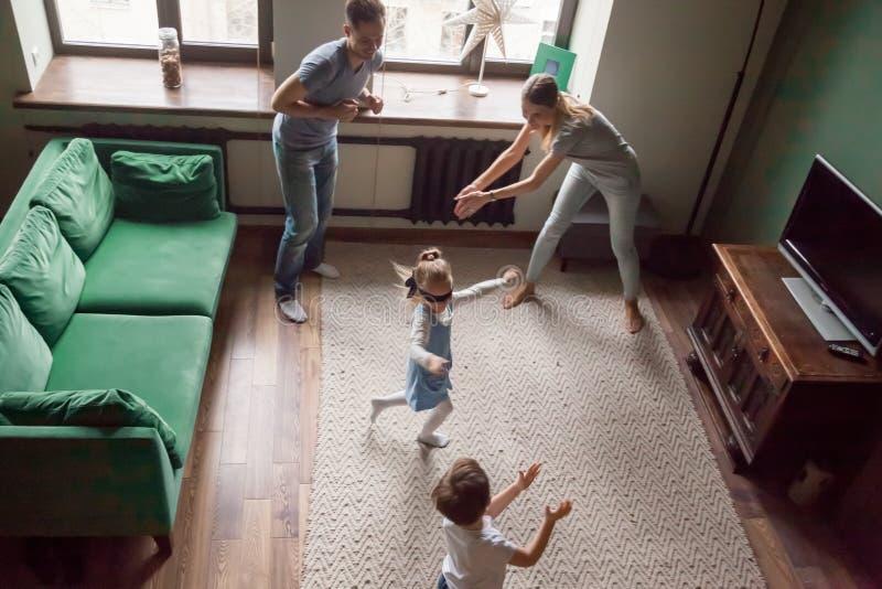 Den lyckliga familjen med barn som spelar kurragömma, spelar tillsammans royaltyfria foton