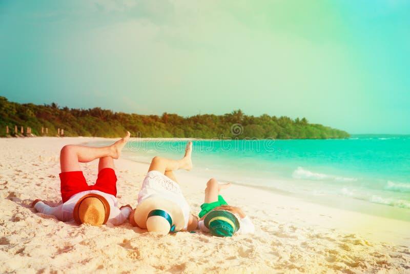 Den lyckliga familjen med barnet kopplar av att ha gyckel på stranden fotografering för bildbyråer