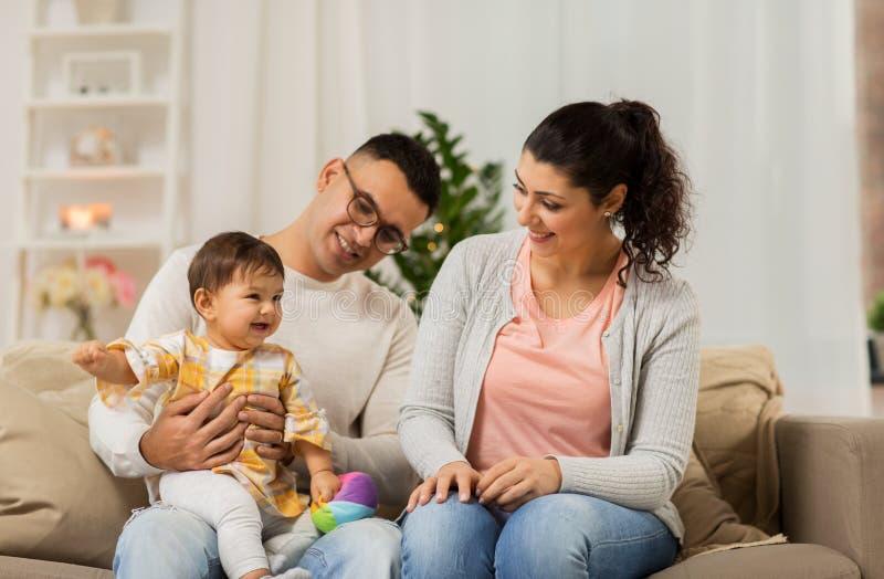 Den lyckliga familjen med behandla som ett barn dottern hemma royaltyfri bild