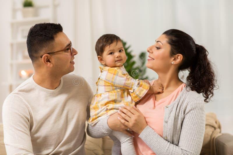 Den lyckliga familjen med behandla som ett barn dottern hemma royaltyfri foto