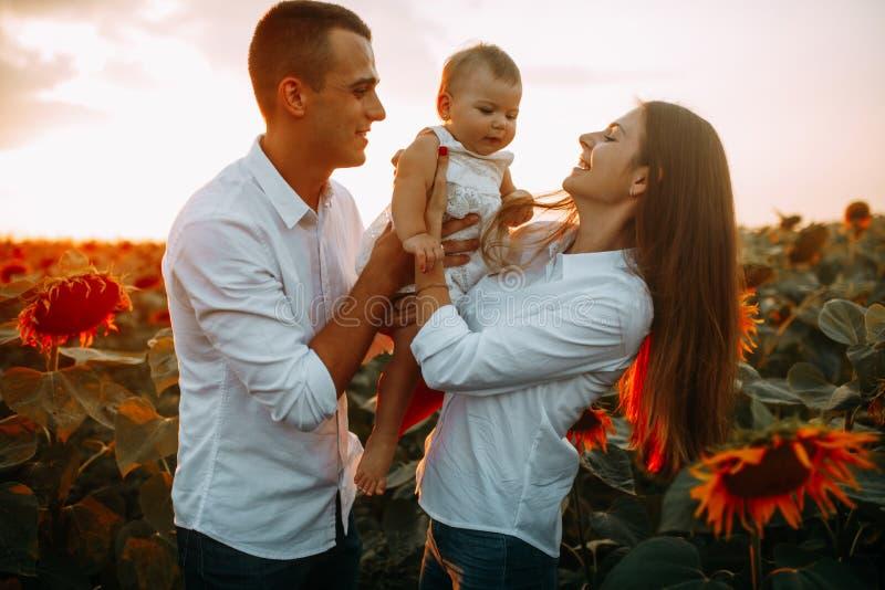 Den lyckliga familjen med behandla som ett barn har en gyckel och lekar i solrosfältet arkivfoton