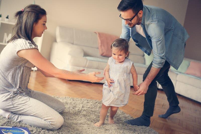 Den lyckliga familjen med deras litet behandla som ett barn hemma arkivbild