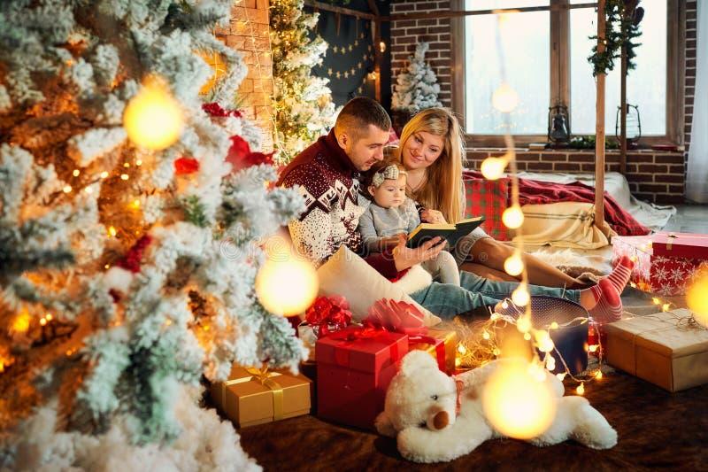 Den lyckliga familjen med en behandla som ett barn i jul hyr rum arkivfoton
