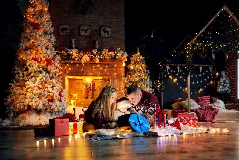 Den lyckliga familjen med en behandla som ett barn i jul hyr rum royaltyfri bild