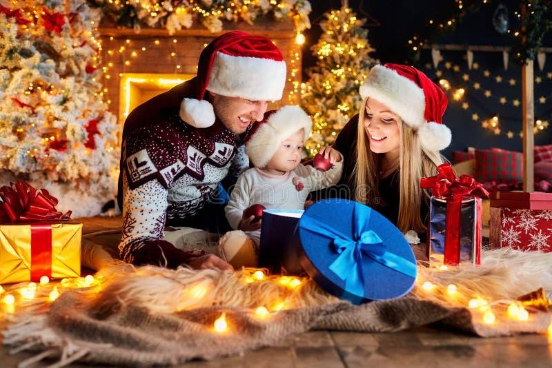 Den lyckliga familjen med en behandla som ett barn i jul hyr rum arkivfoto