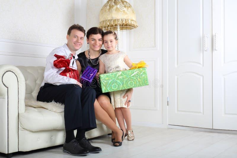 Den lyckliga familjen med gåvor sitter på den vita soffan med gåvor arkivfoton