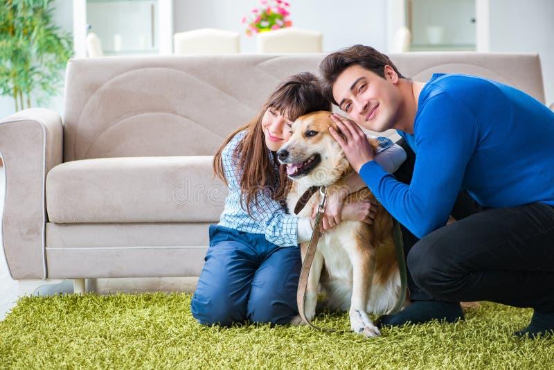 Den lyckliga familjen med golden retrieverhunden royaltyfri fotografi