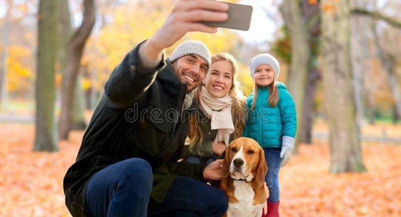 Den lyckliga familjen med hunden som tar selfie i höst, parkerar royaltyfri foto