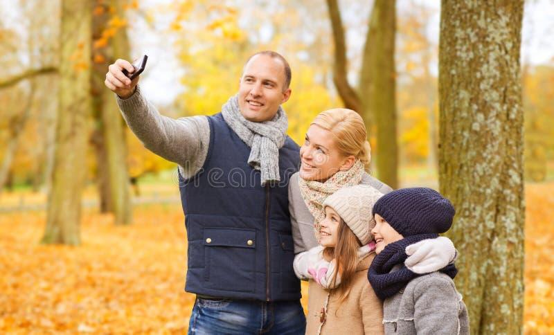 Den lyckliga familjen med kameran i h?st parkerar royaltyfria foton