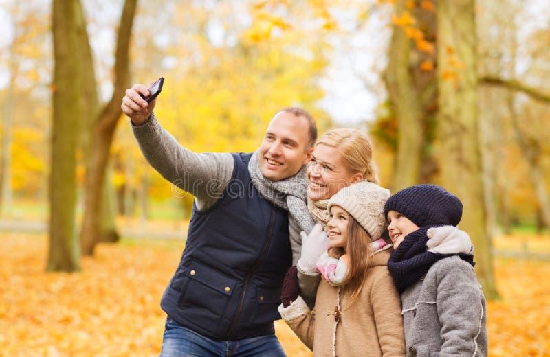 Den lyckliga familjen med kameran i h?st parkerar arkivfoton