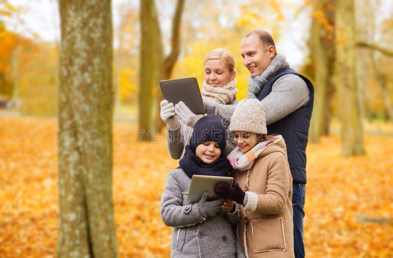 Den lyckliga familjen med minnestavlaPC i h?st parkerar royaltyfria bilder