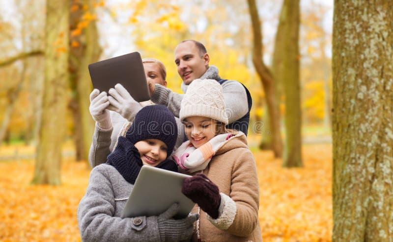 Den lyckliga familjen med minnestavlaPC i h?st parkerar royaltyfria foton