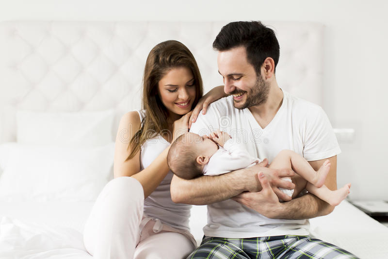 Den lyckliga familjen med nyfött behandla som ett barn på sängen i rum arkivfoton