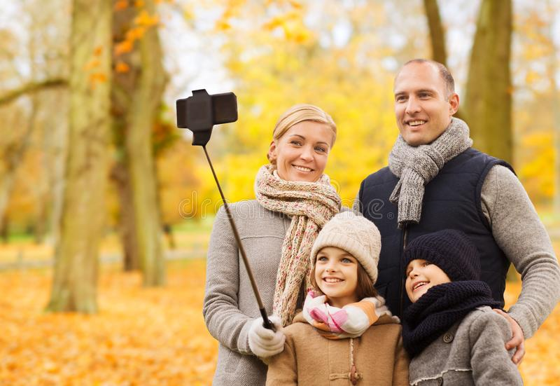 Den lyckliga familjen med smartphonen och monopod parkerar in arkivbild