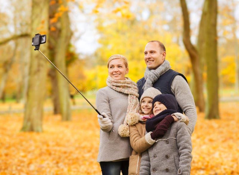Den lyckliga familjen med smartphonen och monopod parkerar in royaltyfria foton