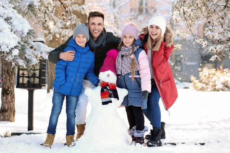 Den lyckliga familjen med snögubben parkerar in royaltyfri bild