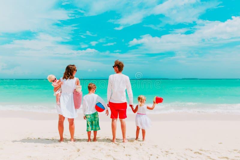Den lyckliga familjen med tre ungar går på stranden arkivbild