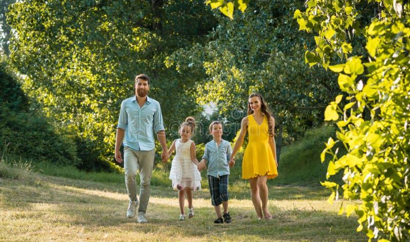 Den lyckliga familjen med två barn som rymmer händer under fritids-, går parkerar in fotografering för bildbyråer