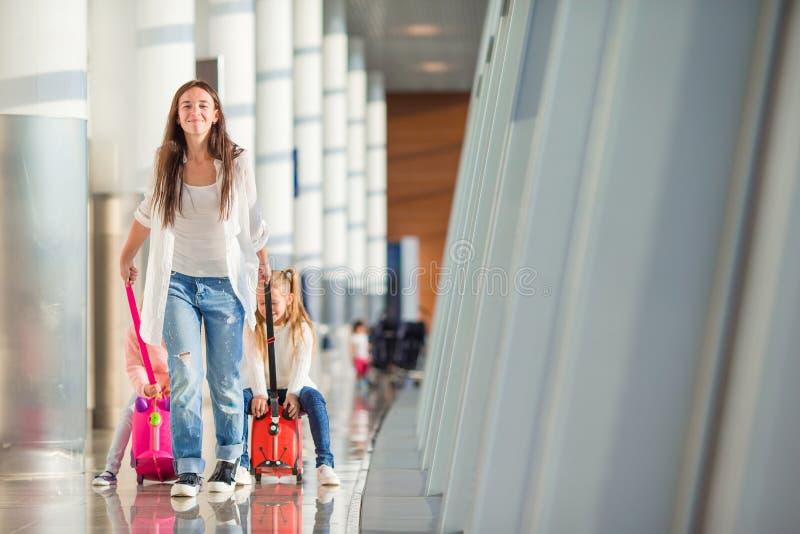 Den lyckliga familjen med två ungar i flygplats har väntande på logi för gyckel royaltyfria foton