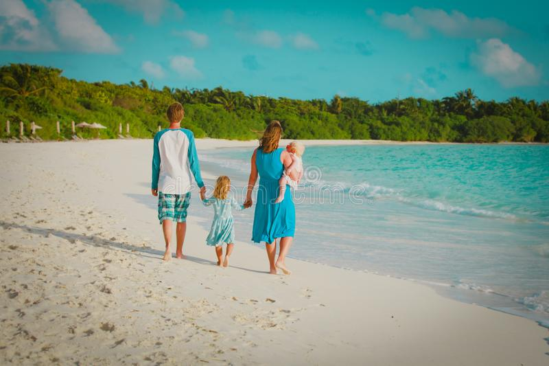 Den lyckliga familjen med ungar g?r p? den tropiska stranden arkivbild