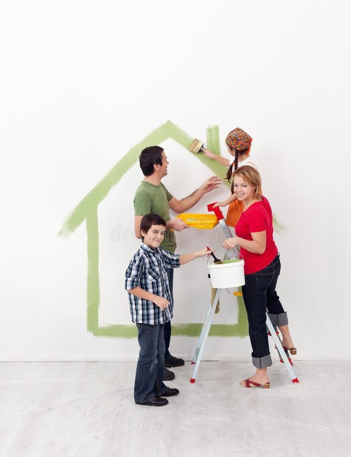 Den lyckliga familjen med ungar nyinreder deras nya hem arkivbilder