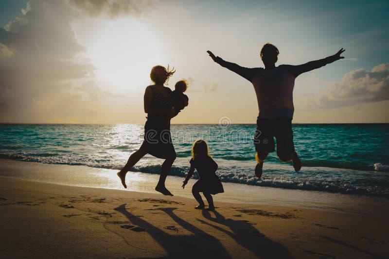 Den lyckliga familjen med ungar tycker om på semestern, lek på solnedgångstranden royaltyfri fotografi