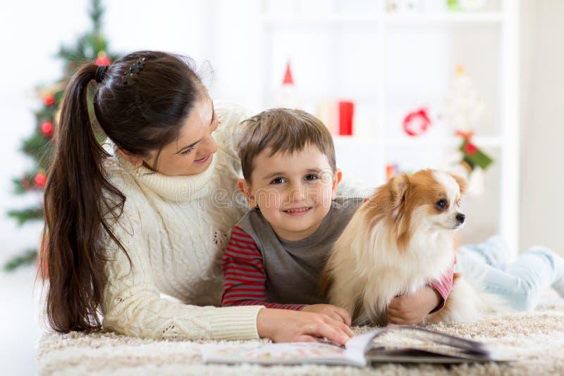 Den lyckliga familjen och hunden som tillsammans spenderar jul, tajmar hemma nära julgranen nytt år för begrepp royaltyfri fotografi