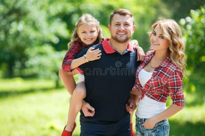 Den lyckliga familjen på en gå parkerar in i sommaren arkivfoto