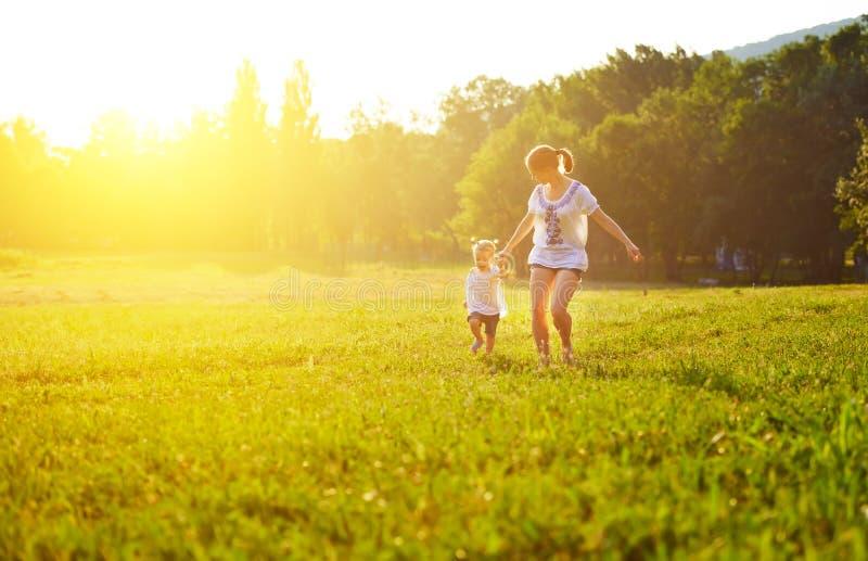 Den lyckliga familjen på naturen går i sommaren fotografering för bildbyråer