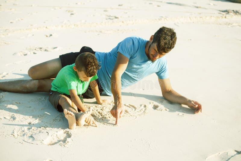Den lyckliga familjen p? stranden som spelar, fader med sonen som g?r havskusten, vaggar bak att le tagande semester fotografering för bildbyråer