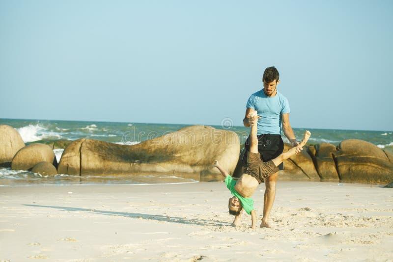 Den lyckliga familjen p? stranden som spelar, fader med sonen som g?r havskusten, vaggar bak att le tagande semester royaltyfria foton