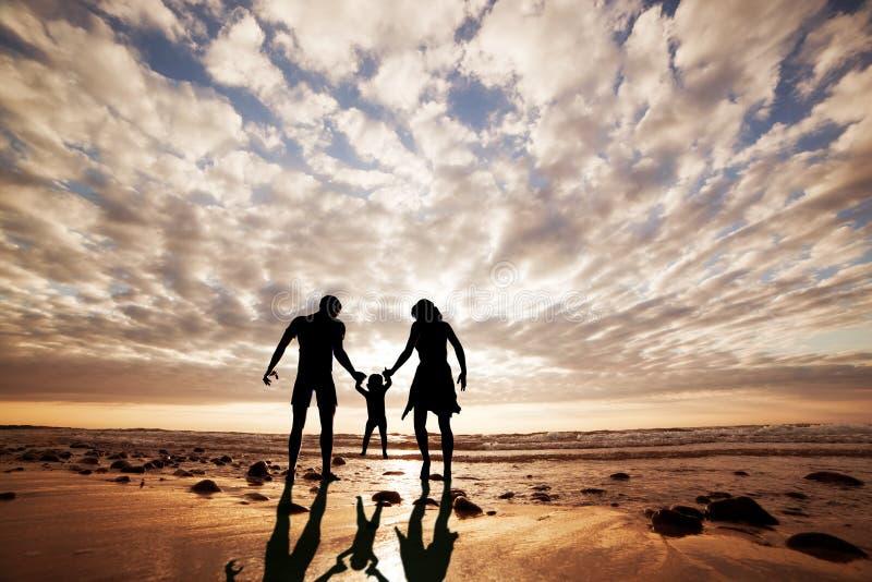 Den lyckliga familjen räcker tillsammans - in - handen på stranden arkivfoto