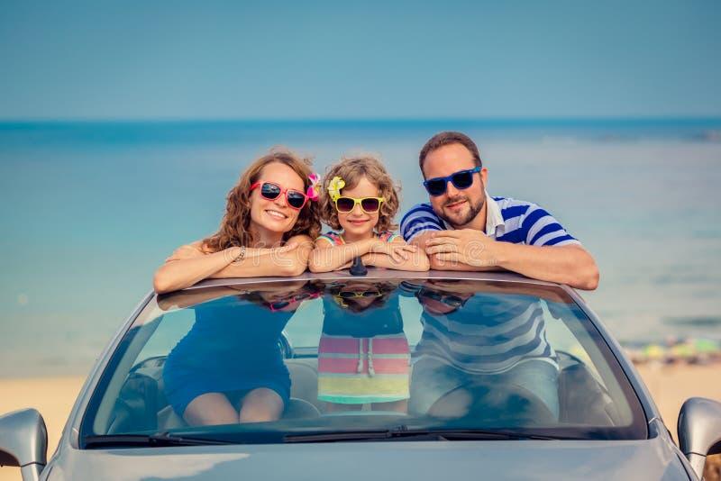 Den lyckliga familjen reser med bilen arkivfoto