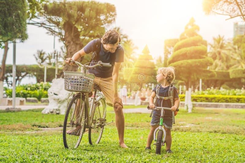 Den lyckliga familjen rider cyklar utomhus och att le Fader på ett b royaltyfria foton