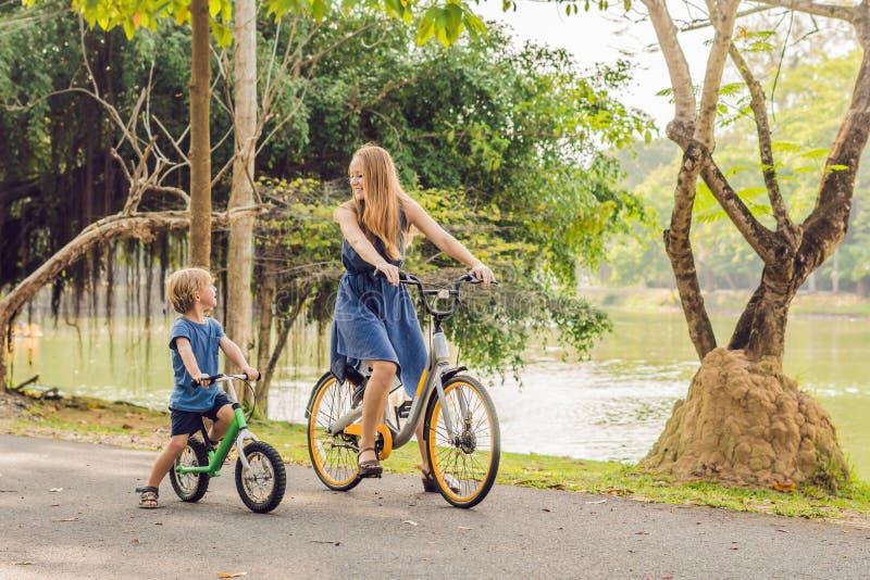 Den lyckliga familjen rider cyklar utomhus och att le Mamma på en cykel arkivbilder