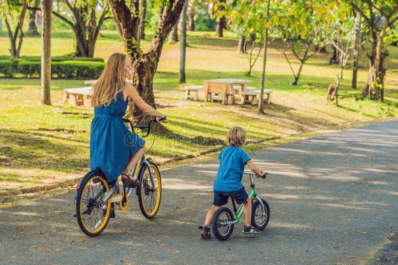 Den lyckliga familjen rider cyklar utomhus och att le Mamma på en cykel och en son på en balancebike royaltyfri fotografi