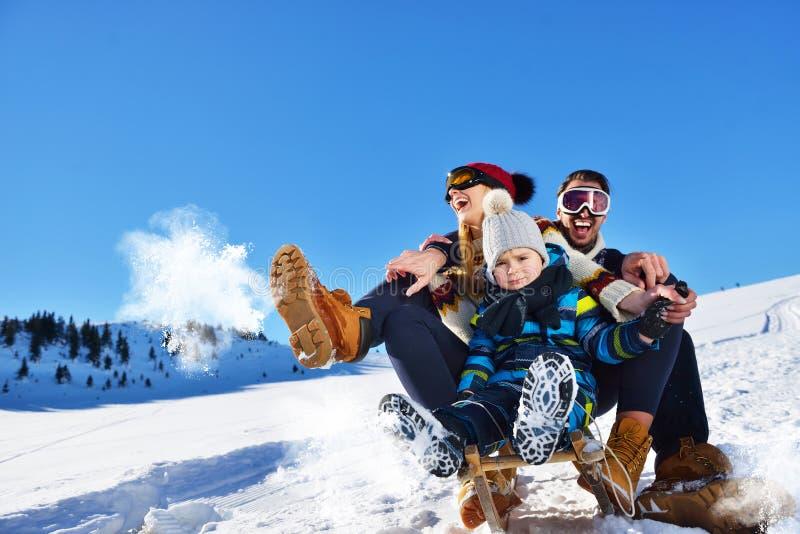 Den lyckliga familjen rider pulkan i vinterträt, gladlynta vinterunderhållningar royaltyfria foton