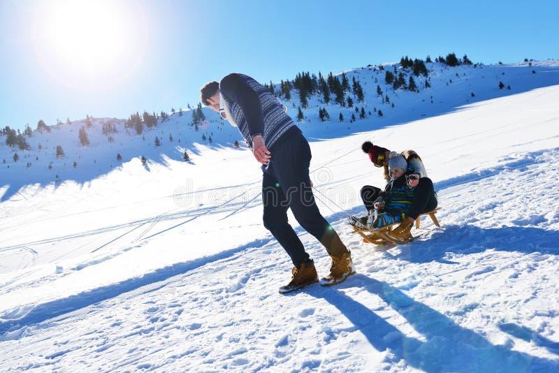 Den lyckliga familjen rider pulkan i vinterträt, gladlynta vinterunderhållningar royaltyfri fotografi