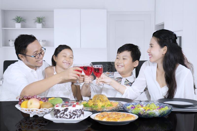 Den lyckliga familjen rostar drinken tillsammans hemma royaltyfri bild