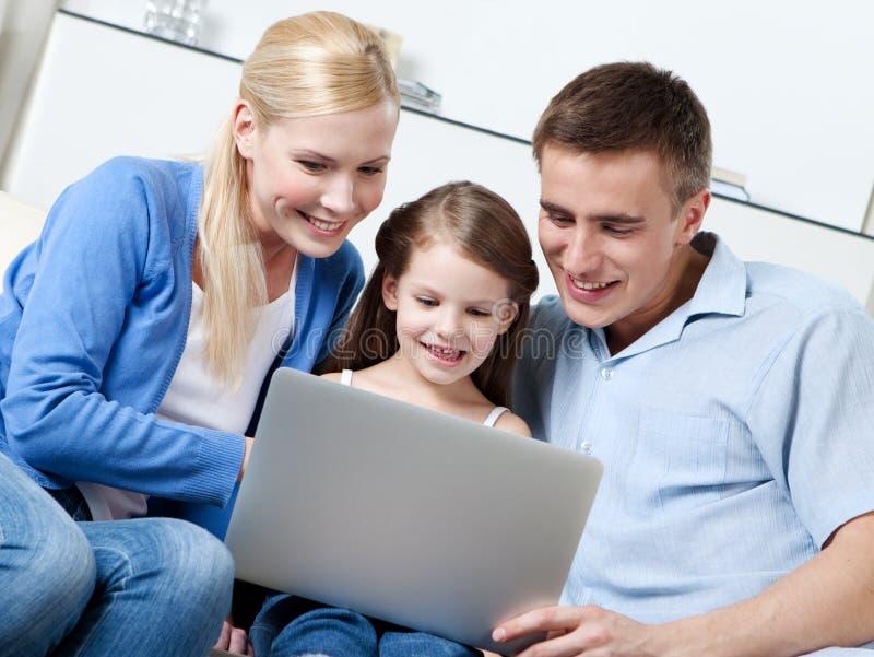 Den lyckliga familjen sitter på sofaen med bärbar dator arkivbild
