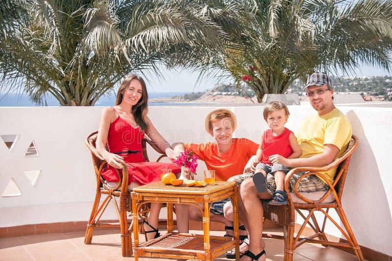 Den lyckliga familjen sitter på terrassen. arkivbild
