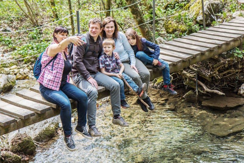 Den lyckliga familjen sitter p? en tr?bro i mitt av skogen arkivfoton